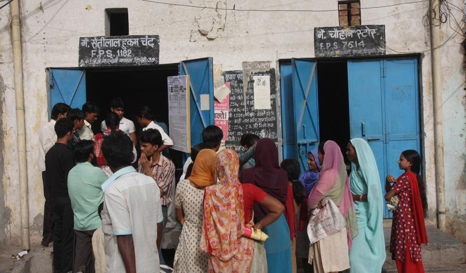 People wait outside a ration shop in Bawana.