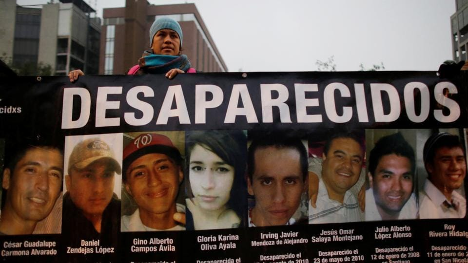 A demonstrator holds a banner with images of her relative and others, who they say went missing or were killed, during a demonstration demanding justice for the victims of violence in Monterrey, Nuevo Leon state, Mexico on December 10, 2016. A sign reading