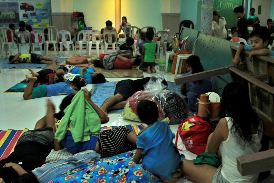 Residents celebrating Christmas Day at the evacuation center take a break before Typhoon Nock-ten strikes Legazpi City, Albay province, central Philippines.