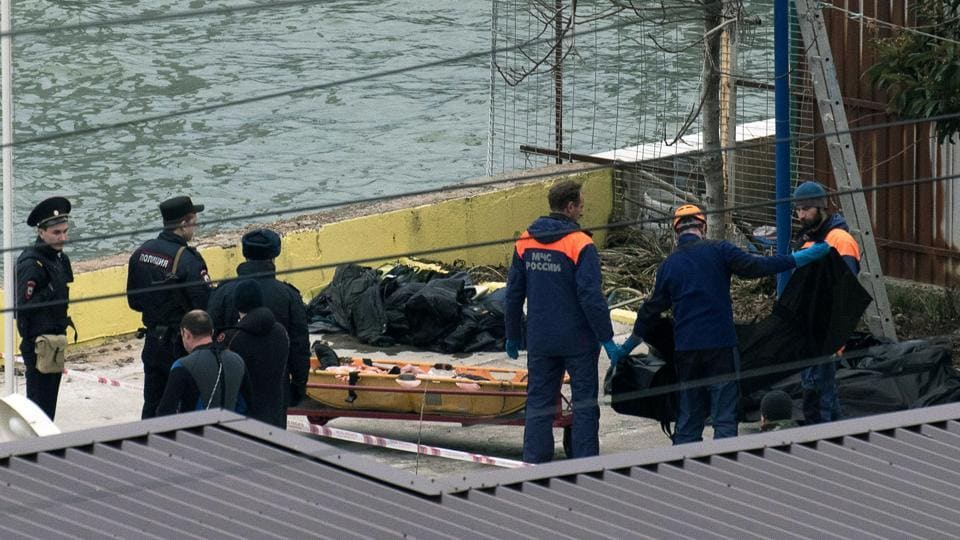 Russian policemen and rescuers stand near a stretcher with a body recovered after a Russian military plane crashed in the Black Sea, on a pier outside Sochi.