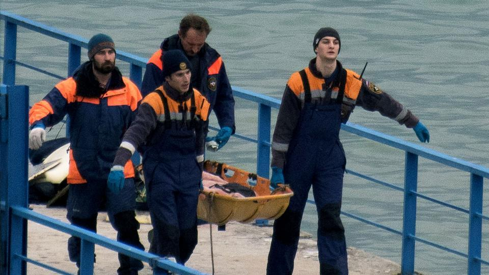 Russian rescuers carry a stretcher with a body recovered after a Russian military plane crashed in the Black Sea, on a pier outside Sochi.