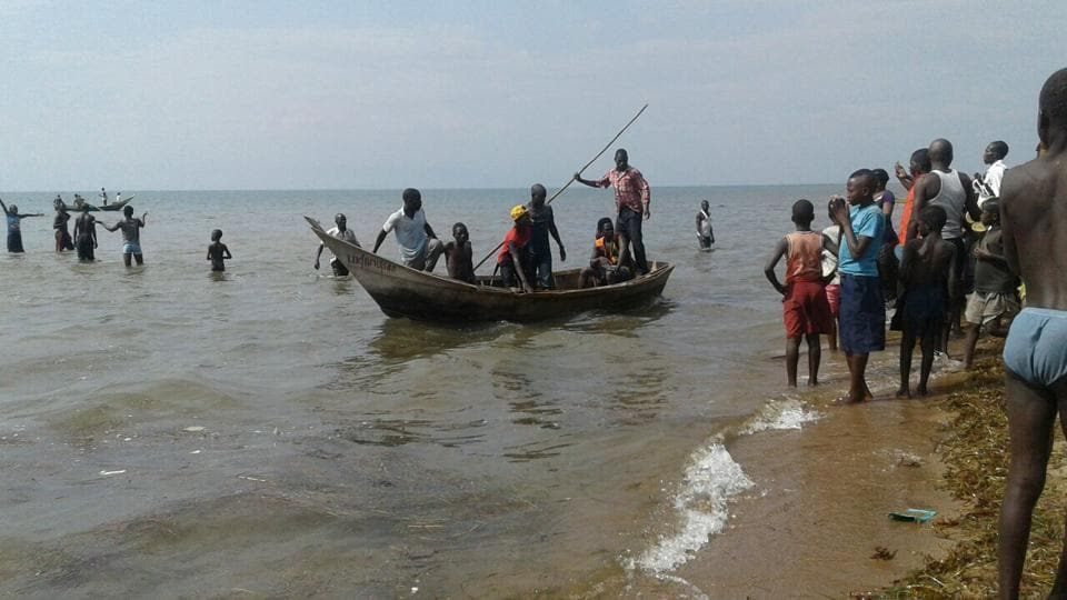 Rescuers are seen on a fishing boat on Lake Albert, on December 26, 2016 in Buliisa, after at least 30 Ugandan members of a village football team and their fans drowned when their boat capsized on Lake Albert during a party.