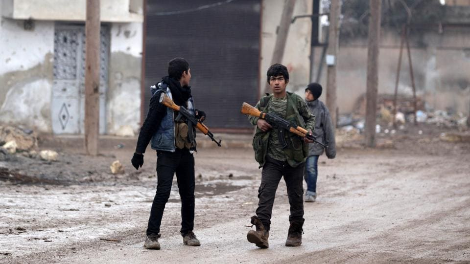 Youth carry weapons along a road in al-Rai town, northern Aleppo countryside, Syria.