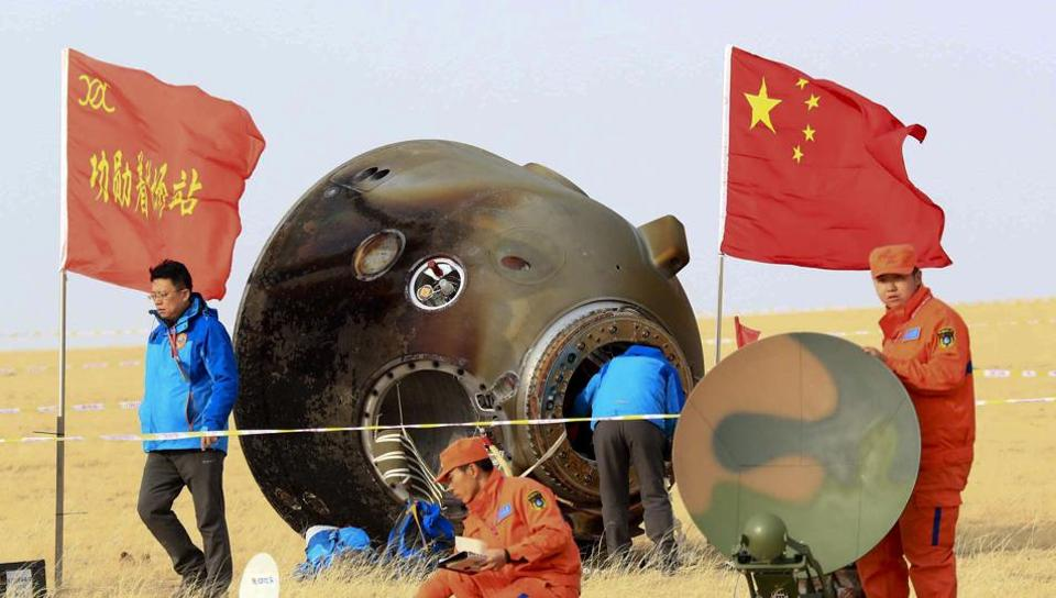 In this Nov. 18, 2016 file photo released, ground crew check on the re-entry capsule of Shenzhou 11 spacecraft, which brought back a pair of Chinese astronauts from a monthlong stay aboard China's space station, after it landed in north China's Inner Mongolia Autonomous Region.