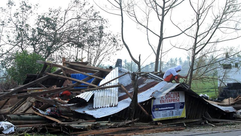 A resident inspects his house which was damaged by Typhoon Nock-Ten in Tabaco. (Charism Sayat/AFP)