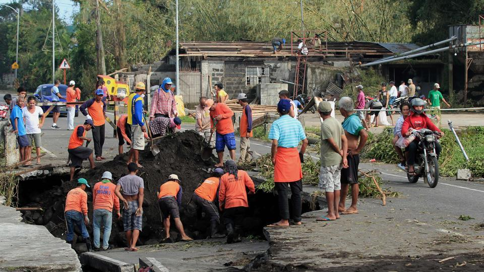 Workers inspect a road damaged that caved in  after Typhoon Nock-Ten hit Tabaco, in Albay province. (Charism Sayat/AFP)