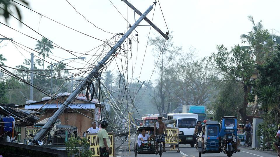 Motorists ride past electric posts damaged by Typhoon Nock-Ten in Tabaco. (Charism Sayat/AFP)