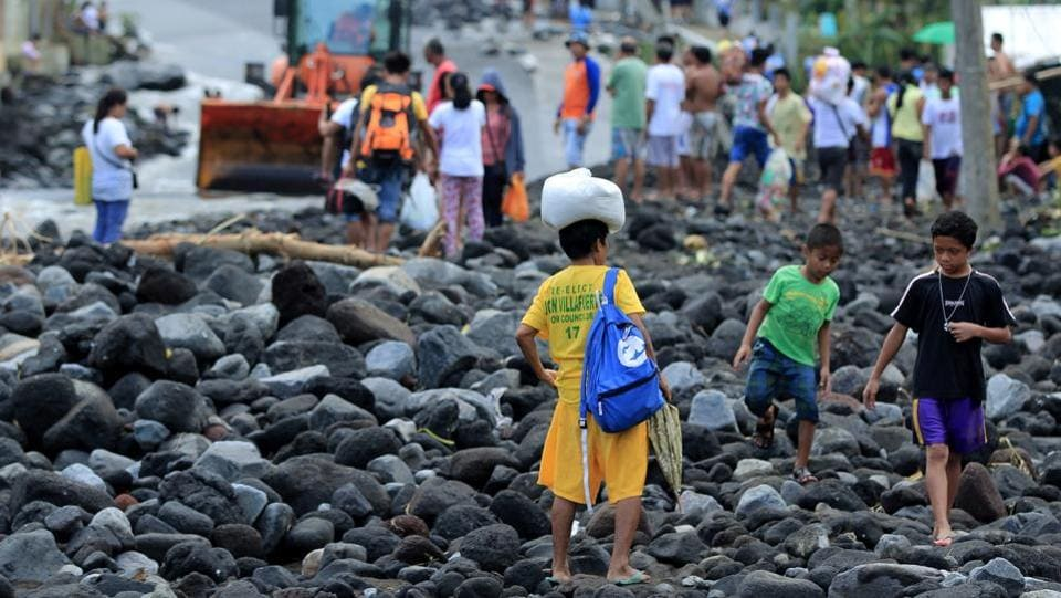 Residents cross a road covered in debris from a landslide triggered by Typhoon Nock-Ten in Tabaco, Albay province . At least six people are dead and 18 others missing after Typhoon Nock-Ten lashed the Philippines over the Christmas holidays, the government said.  (Arlan B. Flores/AFP)
