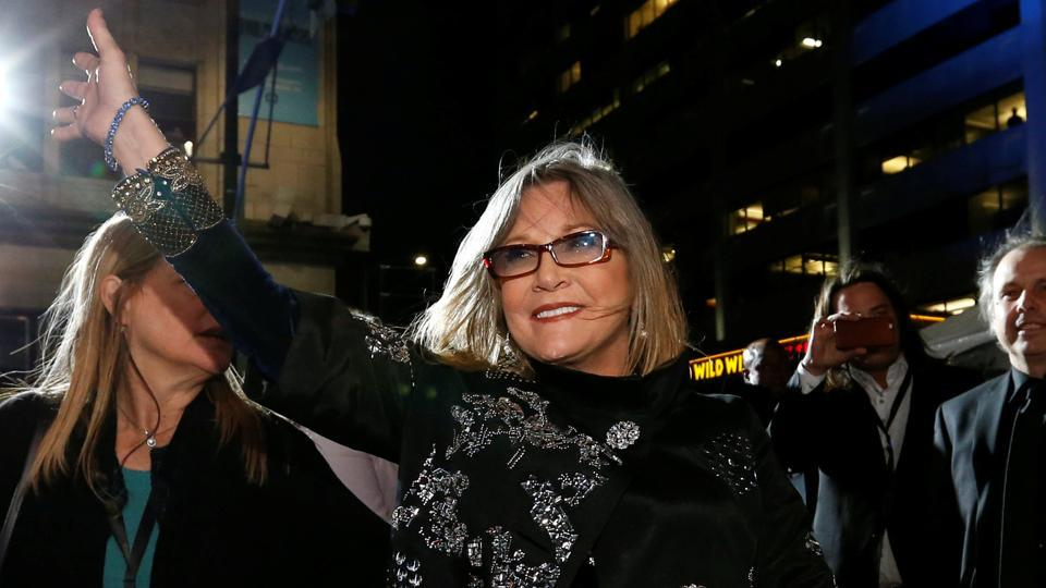 Actress Carrie Fisher waves as she arrives at the premiere of 'Star Wars: The Force Awakens' in Hollywood, California December 14, 2015.The actress passed away on Tuesday, days after suffering a massive heart attack.