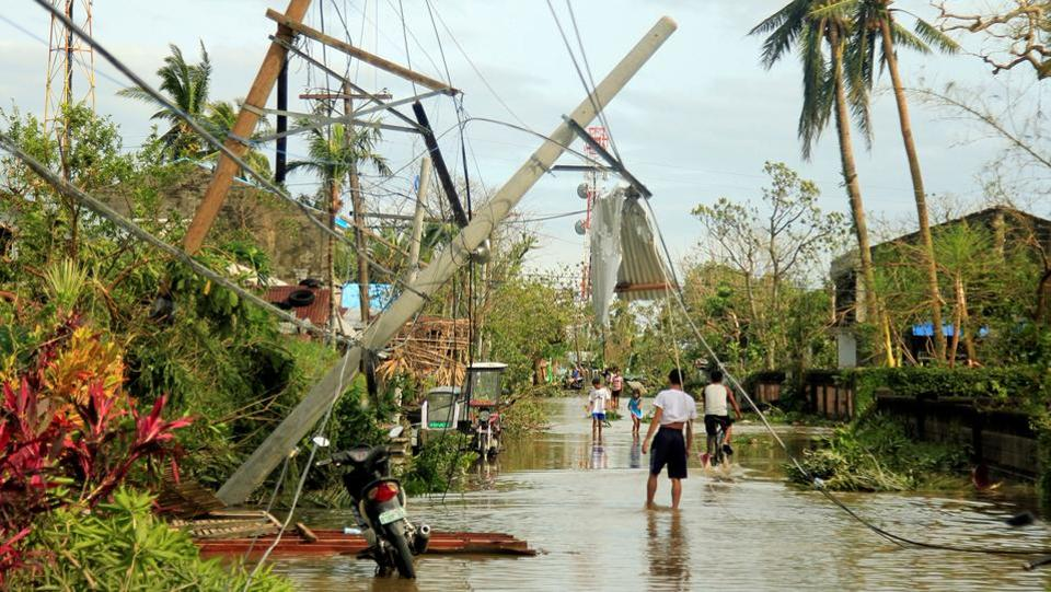 Residents walk past partially toppled electric posts after Typhoon Nock Ten hit Malinao, Albay in central Philippines. (Renellyn Loaquinario/REUTERS)