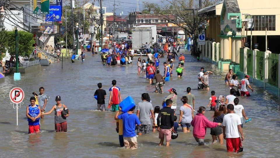 Residents wade across a flooded street brought by heavy rains and strong winds of Typhoon Nock-ten. (Romeo Ranoco/REUTERS)