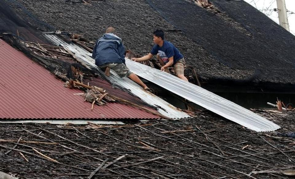 Residents fix their partially damaged roof after Typhoon Nock Ten hit Mabini, Batangas in the Philippines. (Erik De Castro/Reuters)