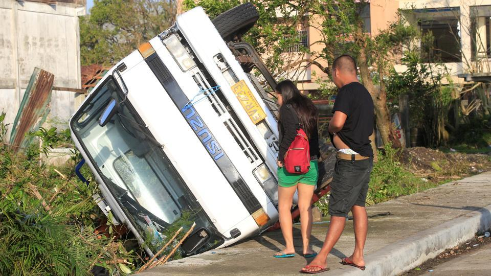 Residents look inside an overturned on a truck after Typhoon Nock-ten hit the city. (Romeo Ranoco/REUTERS)