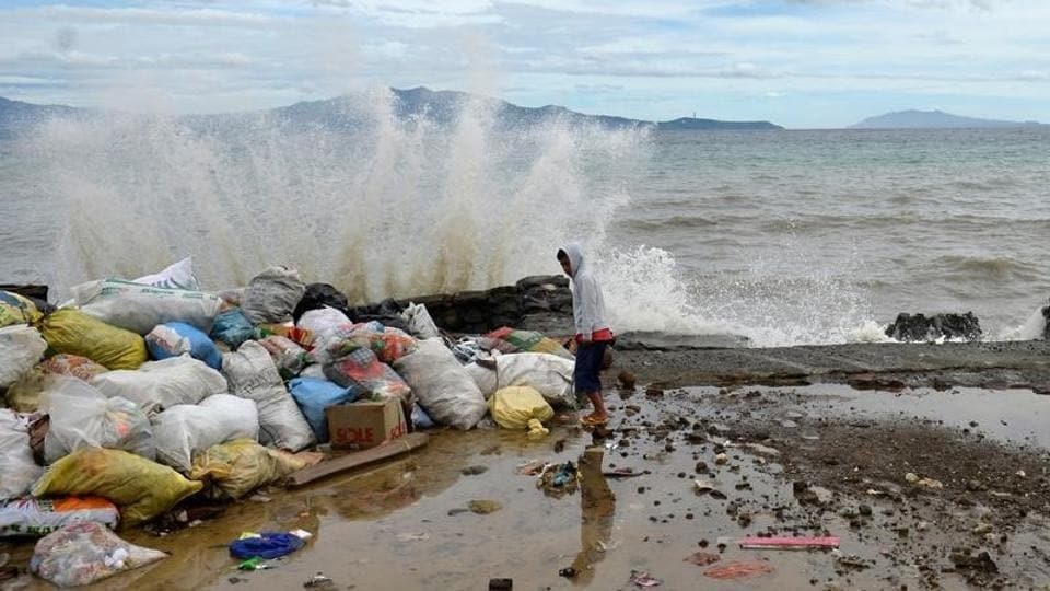 A boy stands at a partially damaged port, as strong waves hit the shore after Typhoon Nock-Ten hit Mabini, Batangas, in the Philippines. (Ezra Acayan/Reuters)
