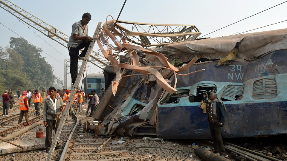 A man cuts an iron frame in front of a damaged coach of a passenger train after it derailed near Kanpur, Uttar Pradesh, on December 28, 2016.
