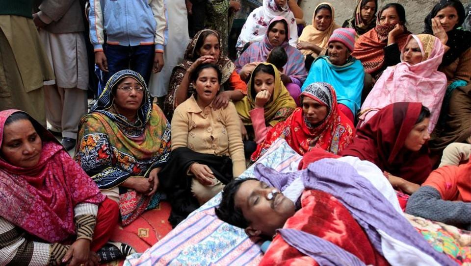 Family members mourn near the body of a man who died after consuming locally made toxic liquor, in Toba Tek Singh, Pakistan.