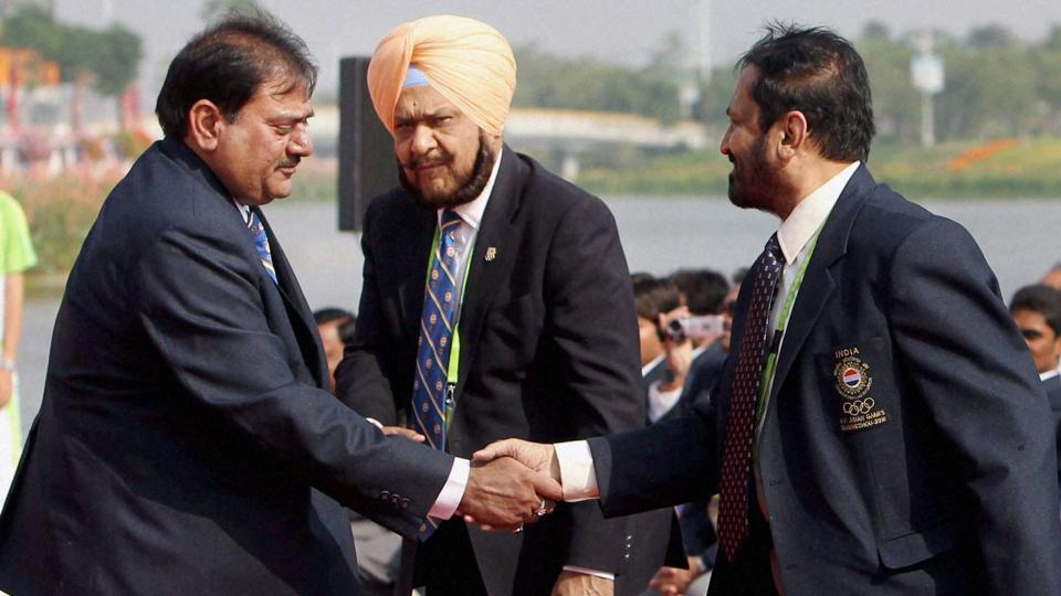 Former Indian Olympic Association president Suresh Kalmadi shakes hands with India's Chef de Mission Abhay Singh Chautala as IOA Secretary-General Randhir Singh looks on during the country's flag hoisting ceremony of the Asian Games 2010 at the Athletes Village in Guangzhou, China.