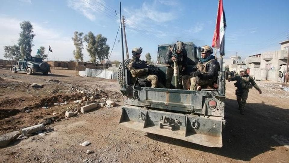 Iraqi rapid response forces ride in a military vehicle during a fight with Islamic State militants in Intisar district of eastern Mosul.