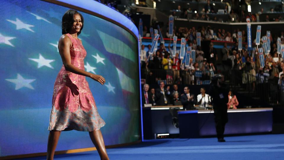 In this Sept 4, 2012 file photo, first lady Michelle Obama, dressed in a Tracy Reese pink silk jaquard dress, walks on the stage at the Democratic National Convention in Charlotte.