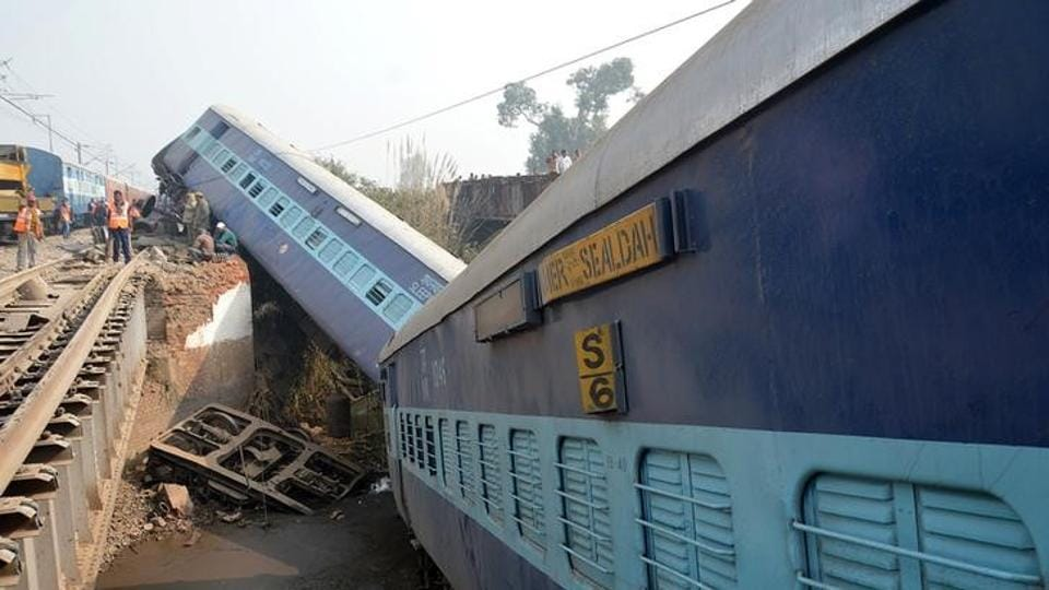 Rescuers and railway officials stand next to derailed coaches of a passenger train near Kanpur.