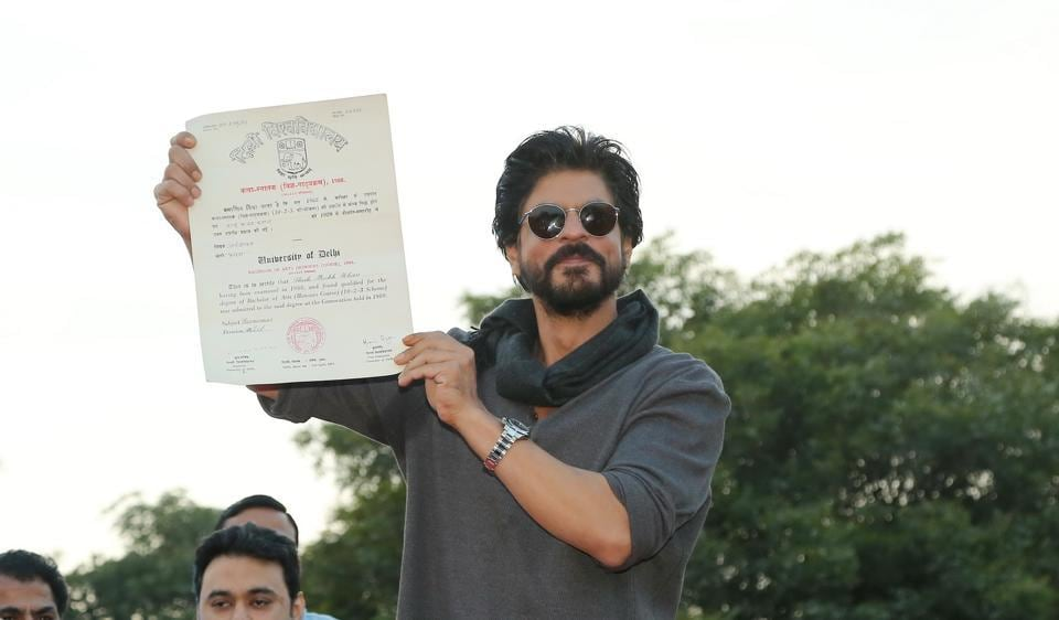 Bollywood actor Shah Rukh Khan poses with his degree on stage at Hansraj college.