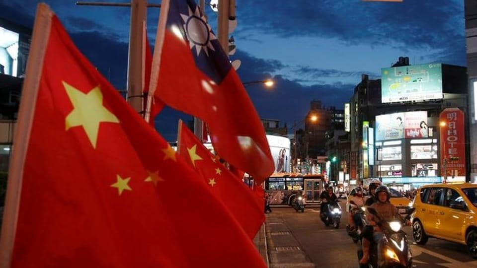 Flags of China and Taiwan flutter next to each other.