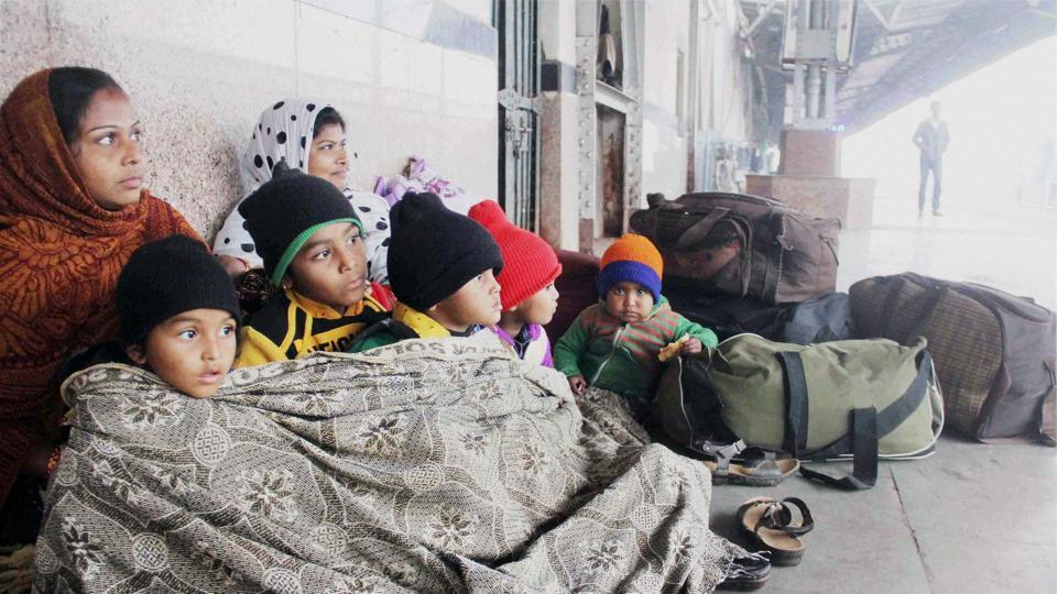 Passengers wrap themselves in woollens as they wait for their trains on a cold and foggy morning at Allahabad Railway Station on Thursday. The fog delayed about 60 trains while 20 were rescheduled in north India.