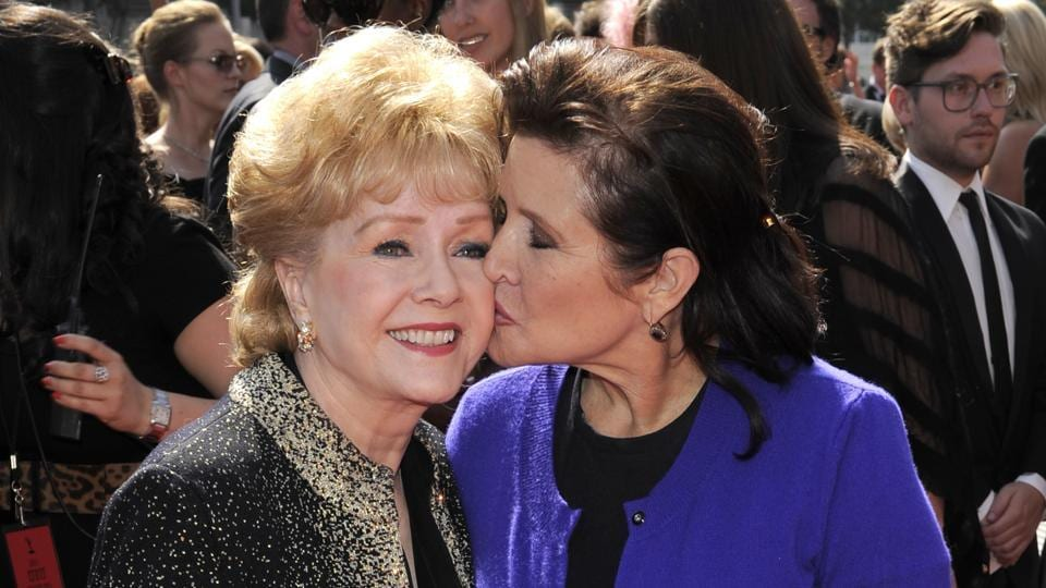 In this September 10, 2011, file photo, Debbie Reynolds, left, and Carrie Fisher arrive at the Primetime Creative Arts Emmy Awards in Los Angeles. Reynolds, star of the 1952 classic