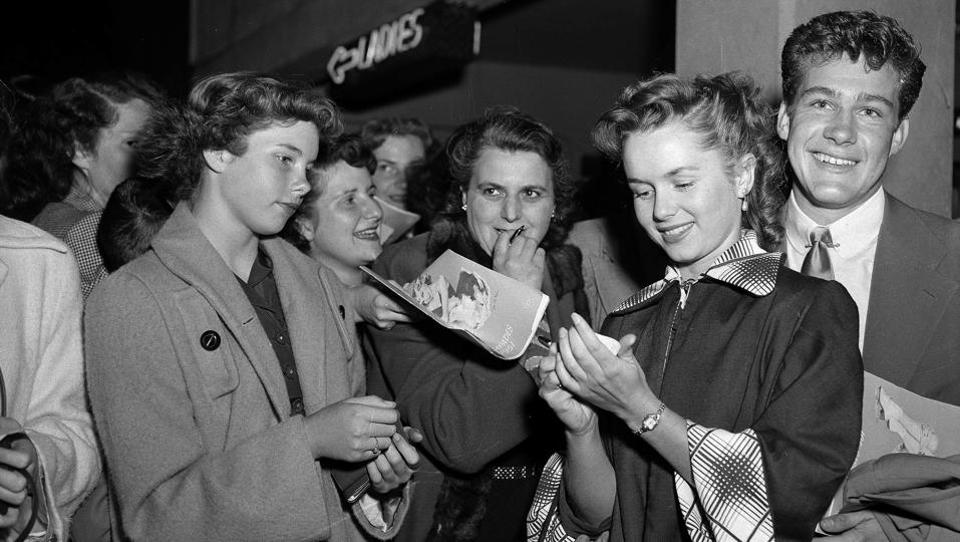 In this May 7, 1951, file photo, actress Debbie Reynolds signs autographs on her way into the ice show in the Hollywood section of Los Angeles.  (AP File Photo)