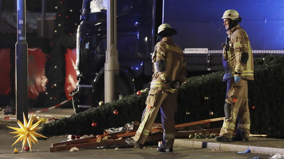 In this December 19, 2016 file photo firefighters look at a toppled Christmas tree after a truck ran into a crowded Christmas market in Berlin.