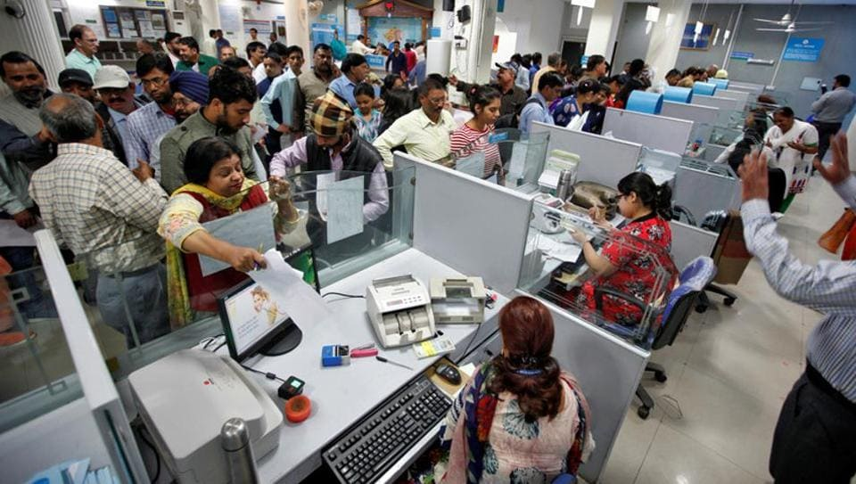 People stand in queues at cash counters to deposit and withdraw money inside a bank in Chandigarh.
