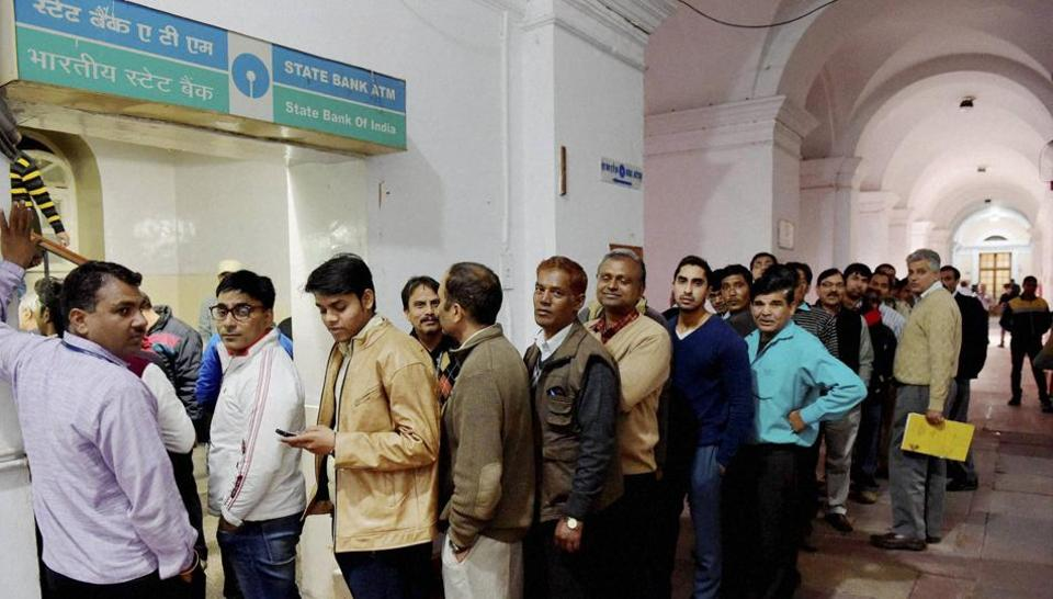 Employees of finance ministry stand in a queue to withdraw cash from an ATM at North Block in New Delhi.