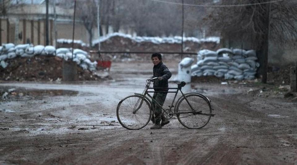 A boy walks his bike near stacked sandbags in al-Rai town, northern Aleppo province, Syria.