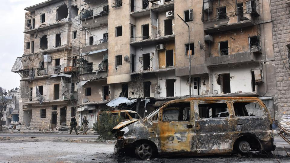 Syrian government forces walk past destroyed buildings in the former rebel-held Ansari district in the northern Syrian city of Aleppo on December 23, 2016 after regime forces retook control of the whole embattled city.