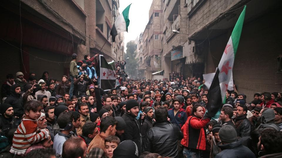 Syrian demonstrators gather in the rebel-held town of Saqba, on the eastern outskirts of the capital Damascus, during a demonstration in solidarity with the inhabitants of the embattled Syrian city of Aleppo on December 16, 2016.