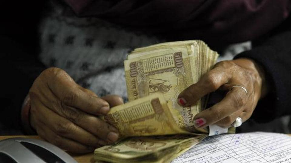 In this Dec. 16, 2011 file photo, a cashier counts Rs 500 notes at a bank in Allahabad.