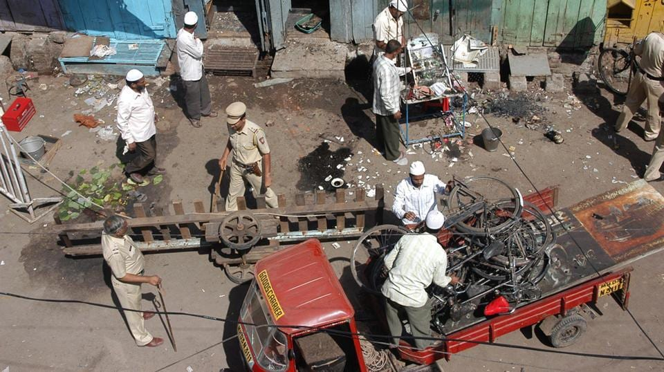 A file photo of local residents and police officers clearing debris at a blast site in Malegaon on September 30, 2008.