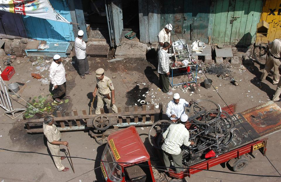 Locals  and police officers clear debris at a blast site in Malegaon.