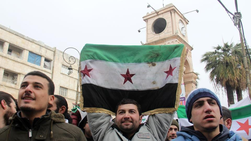 Dozens of Syrians take part in a small gathering calling for the fall of the regime on Friday in the northwestern city of Idlib.