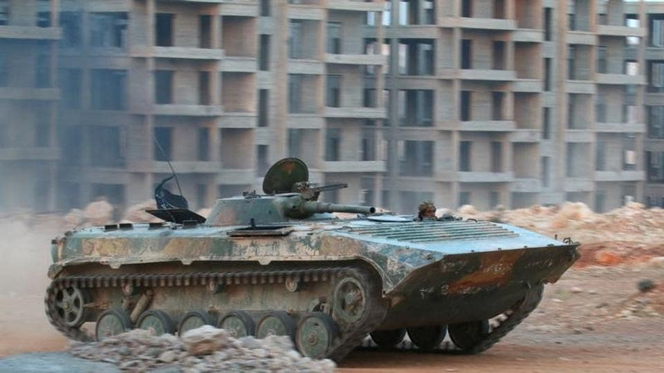 A fighter of the Syrian Islamist rebel group Jabhat Fateh al-Sham rides in an armoured vehicle in the 1070 Apartment Project area in southwestern Aleppo, Syria.