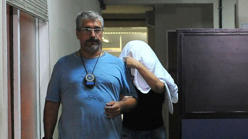 A Brazilian civil policeman escorts the wife of Greece's ambassador to Brazil Kyriakos Amiridis, Francoise de Souza Oliveira, who murdered him in a plot hatched with her police officer lover, who confessed to the crime, on December 30, 2016 in Rio de Janeiro.