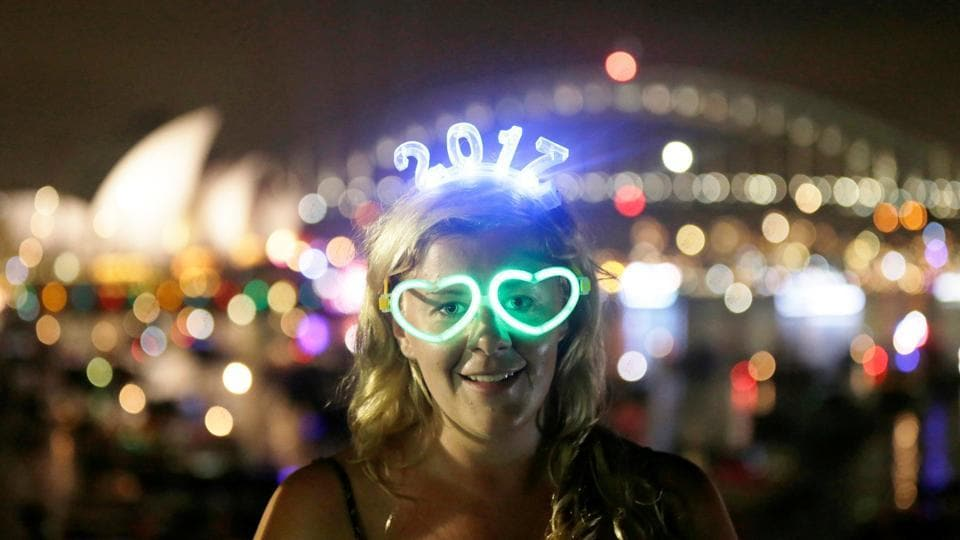 """Celebration mode on!""  A woman watches the fireworks in Sydney through her glowing glasses. (REUTERS)"