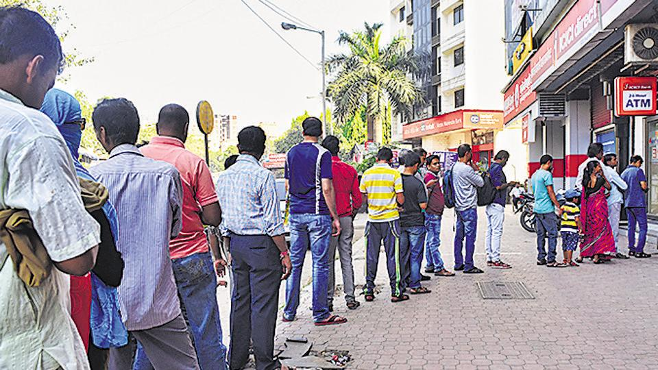 People stand in queue outside a bank ATM to withdraw money in Mumbai on December 10, 2016. Such queues had become a common sight after November 8, the day PM Narendra Modi announced demonetisation.
