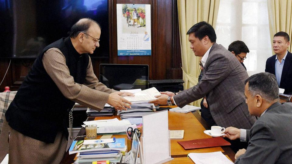Union finance minister Arun Jaitley receives some documents from chief minister of Arunachal Pradesh Pema Khandu at his office in North Block in New Delhi on Thursday.