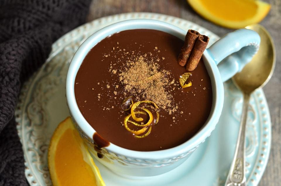 A cup of hot cocoa with cinnamon and orange zest.