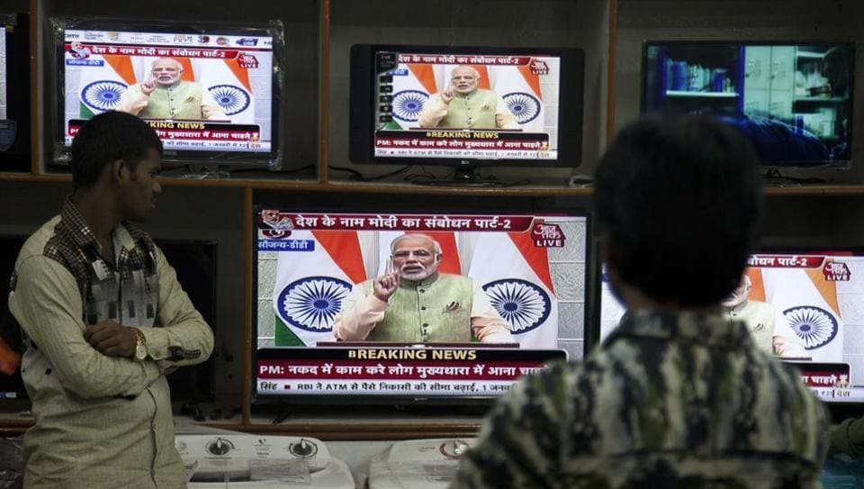 People watch Prime Minister Narendra Modi addressing the nation in Hyderabad, on December 31, 2016.