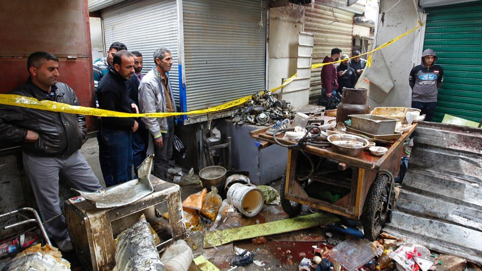 Iraqis look at the aftermath following a double bomb attack in a busy market area in Baghdad's central al-Sinek neighbourhood on December 31, 2016.