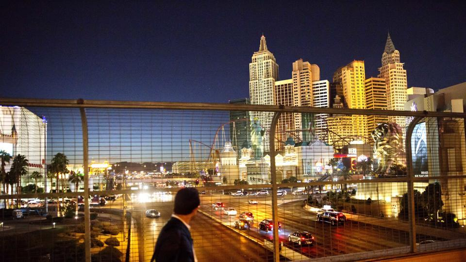FILE - In this Oct. 18, 2016 file photo, the Las Vegas Strip is seen in the background as a pedestrian passes in Las Vegas. More than 300,000 visitors are expected to descend on Las Vegas for an extravagant New Year's Eve celebration. Nightclubs are pulling out all the stops with performances from DJ Calvin Harris, rappers T-Pain and Kendrick Lamar and artists Drake and Bruno Mars. (AP Photo/David Goldman, File) (AP)