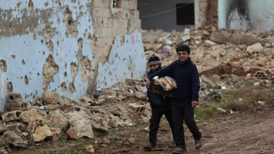 Boys carry bread near damaged buildings in al-Rai town, northern Aleppo countryside, Syria December 30, 2016. A ceasefire, brokered by Turkey and Russia, was announced on Dec 30, 2016.
