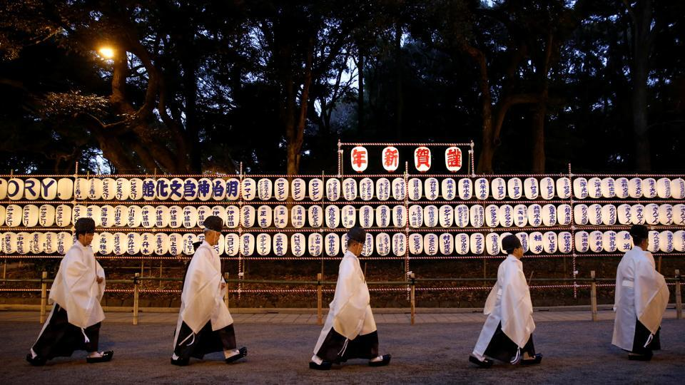 Shinto priests walk past lanterns after attending a ritual to usher in the upcoming New Year at the Meiji Shrine in Tokyo (Reuters)